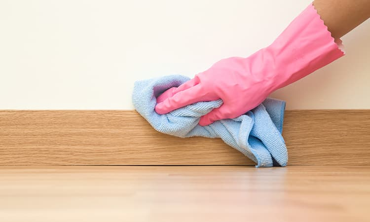 cleaning baseboard with towel