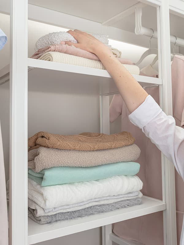 stacking clothes on shelf