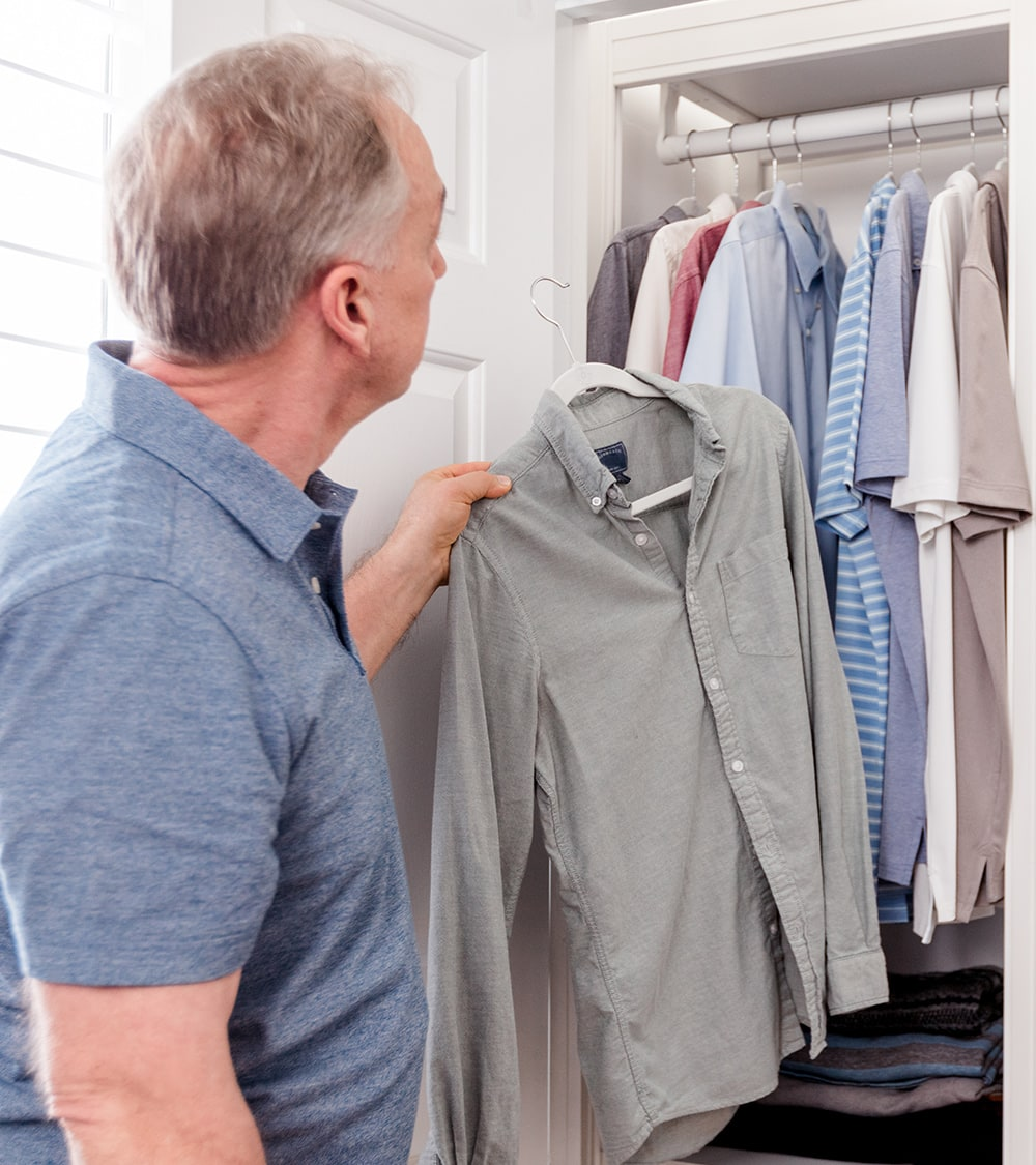 man placing shirt in closet