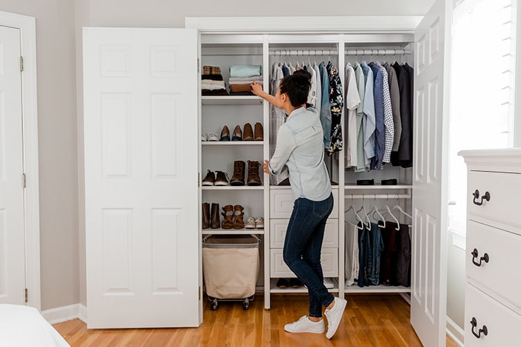 woman adjusting clothes in closet