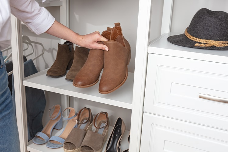 Person picking up boots from flat shoe shelf