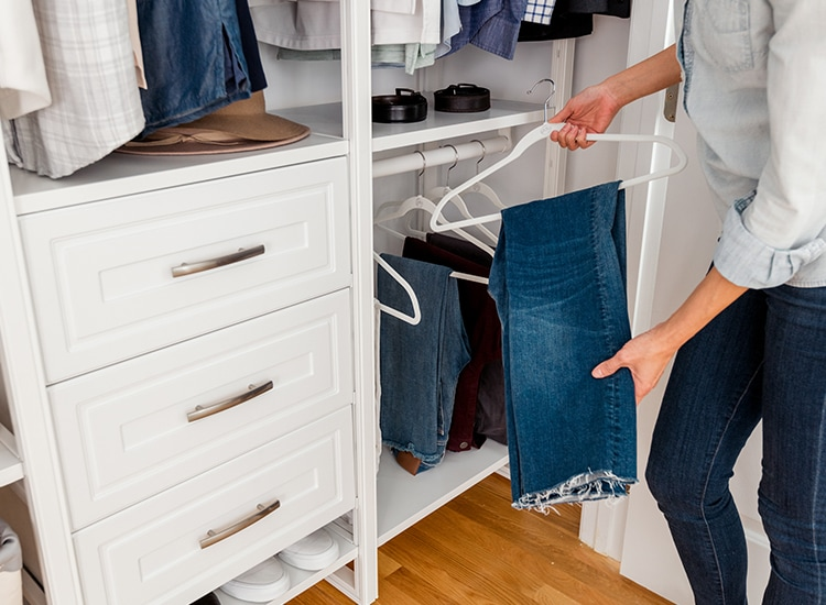 Woman holding jeans on a hanger