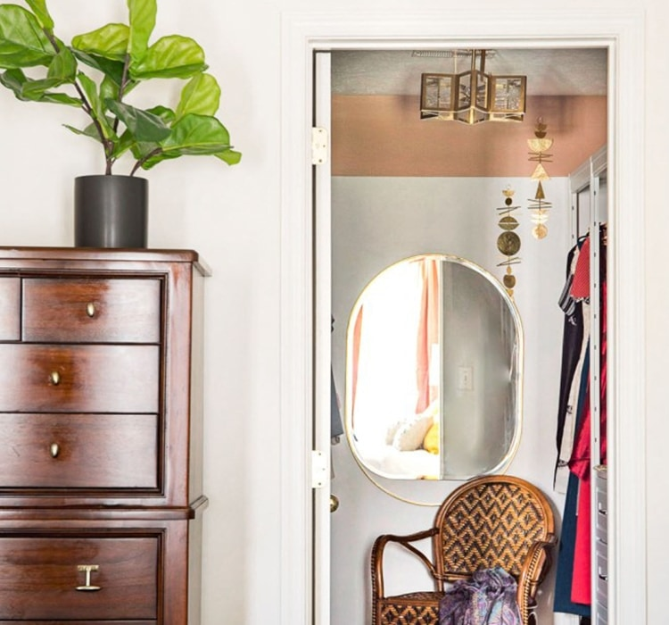 Oval mirror and chair inside walk-in closet