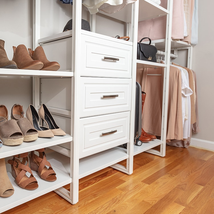 White floor based closet system with shoes and hanging clothes