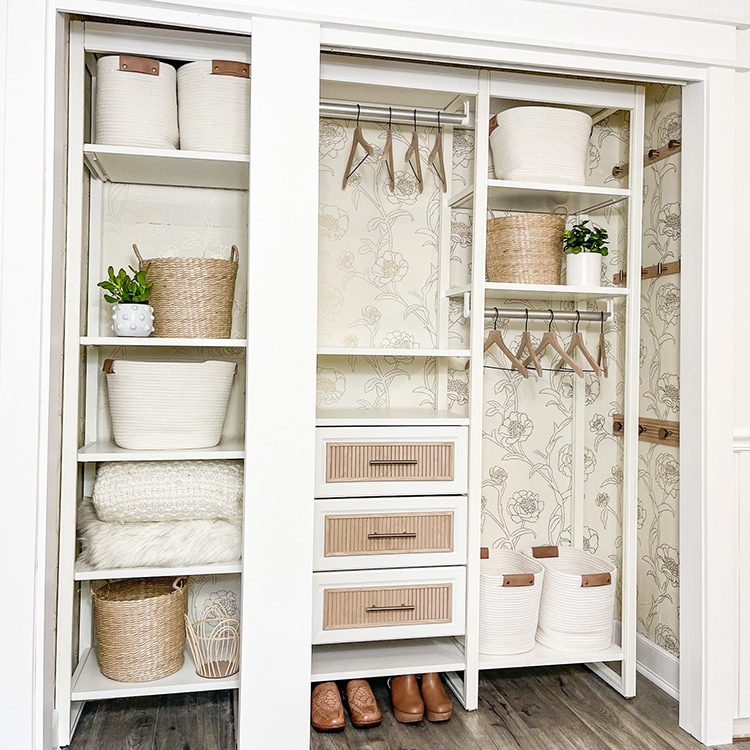White reach-in closet with floral wallpaper