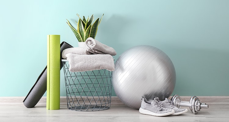 Set of sports equipment with fitness ball, yoga mats and sneakers near wall